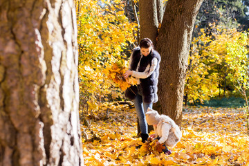mom and daughter toss the autumn leaves upwards