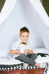 A cute little boy is playing with paper boats at home in a children's tent. Children's room decorated with pompons and paper garlands. Children's holiday