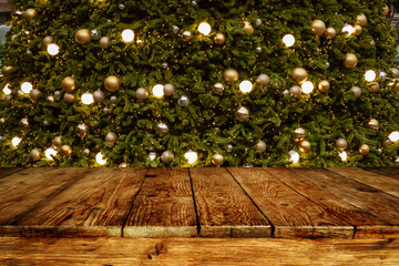 Wall Mural - Christmas and New year background with empty wooden deck table over blurred christmas tree at night. Empty display for product montage. Rustic scene.