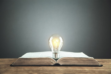 Open book with light bulb. Idea, knowledge and education