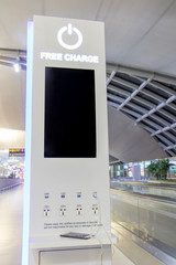 Free battery charging station in the airport for traveler. Phone charging on a table at charging station in the lobby. Free charging on the airport terminal.