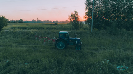 Aerial view of the tractor in the field. Harvesting. Ukraine.