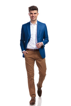 relaxed young smart casual man walking forward