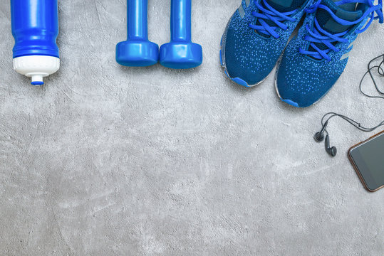 Sport concept background. Sneakers, dumbbells,  water bottle and phone with headphones. Sport and healthy, backdrop for design with copy space.