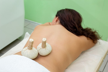 Woman having spa bags massage in wellness salon