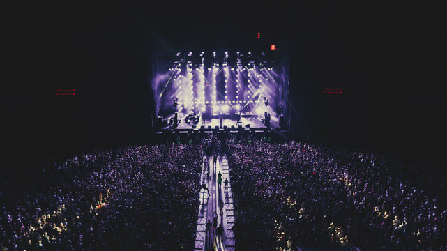 Aerial view on the stage. Music Festival. Crowds of people. Evening. Night. Dark.