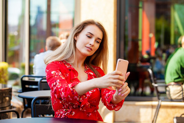 Beautiful young woman taking pictures of herself on a cellphone