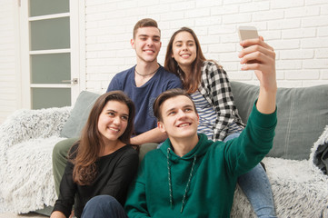 A company of teenagers makes selfies