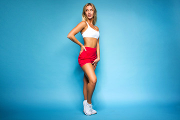 young sports happy sexy blonde girl in red skirt and white top is standing like athlete and smiling excited on the blue wall background