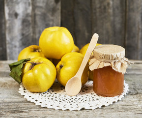 close up of jar of jam and quinces with leaves on wooden rustic background.