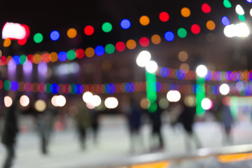 Blurred texture. People skate in the evening on a city skating rink.