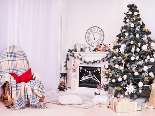 Xmas Tree and Fireplace with armchair, gifts, clocks and pillows. Christmas stocking over fireplace, New Year's card scenery. Snowman and stars. New Year concept.