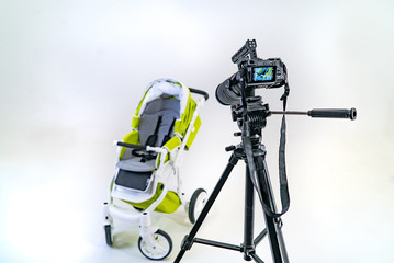 professional camera is focused on a green pram that stands on a white background of room