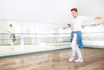Modern art dancer dressed in white clothes listening a music with smartphone and dancing in mirror hall