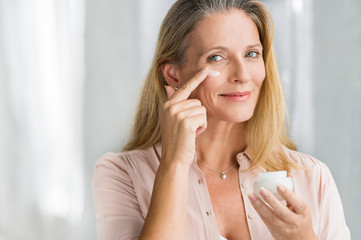 Woman applying anti aging lotion on face