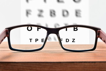 Glasses on table and alphabet letter front view