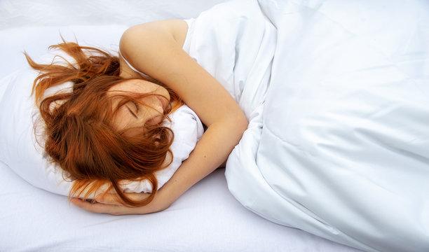 Draufsicht der attraktiven, jungen, rothaarigen Frau, die im Bett ein weiches weißes Kissen umarmt, schläft, genießt frische weiche Bettwäsche im Schlafzimmer mit freiem Raum für Ihren Text