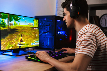 Image of young man playing video games on computer, wearing headphones and using backlit colorful keyboard