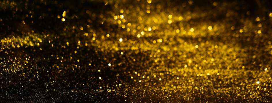 Blurred background lights. Abstract defocused gold, white, red and yellow glitters texture on black background. Shining glowing snow effects