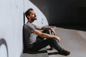 Entspannter Mann sonnt sich mit geschlossenen Augen und lehnt mit dem Rücken an der Wand