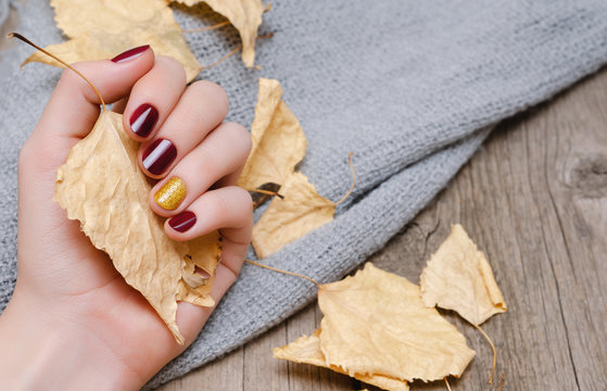 Female hand with dark red nail design