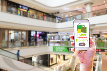 Hand holding smart phone for shopping online on cyber monday of concept with department store background - Cyber Monday Shopping of concept