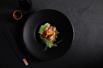Fototapeta top view of delicious traditional japanese dish with seafood, avocado and herbs on black plate obraz