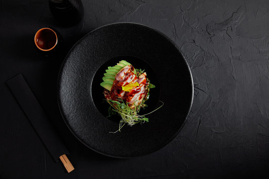 top view of delicious traditional japanese dish with seafood, avocado and herbs on black plate