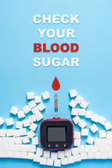 inscription check your blood sugar, red blood drop, wall made of sugar cubes ruined by Glucose meter on blue background