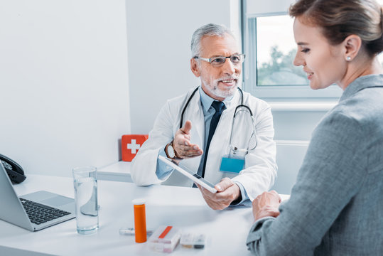 smiling middle aged male doctor with digital tablet gesturing by hand and talking to female patient at table in office