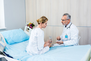 middle aged male doctor with stethoscope over neck pointing at pills to female patient in hospital room