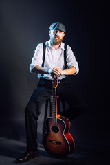 A bearded man in hat with guitar in studio