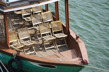 Wooden chairs lined up on the deck of a tour boat in Southeast Asia