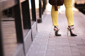 a girl in high heels is standing on the street. Close up photo of woman's legs in high heels