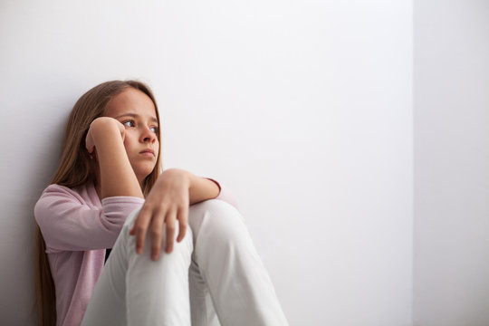 Pensive young teenager girl sitting by the wall on the floor