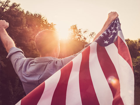 Attractive man holding a US flag against the background of the rays of the setting sun. View from the back. Preparing for the holidays