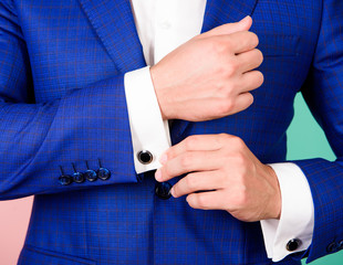 Make sure outfit and appearance look perfect. Detail make outfit elegant. Male fashion. Perfect to last detail. Male hand check button on shirt sleeve. Cufflinks match with luxury classic suit jacket