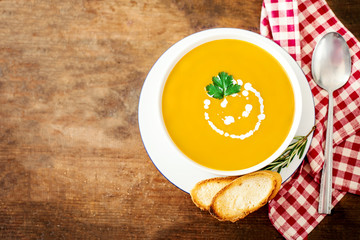 Bowl of vegetable yellow soup with parsley and croutons over wooden background.  Autumn Pumpkin and carrot soup with cream. Copy space.