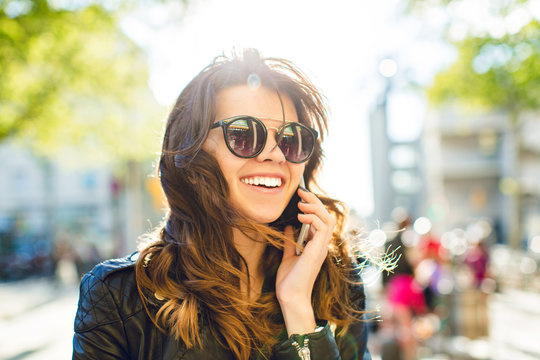 Closeup portrait of positive brunette girl speaking on phone on windy sunny street . She wears sunglasses, black jacket, smiling to side.