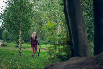 Girl in pullover with black umbrella walk in county side village outdoor natural landscape environment autumn season time with creative concept shot between trees