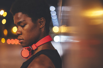 Portrait of  young confident afro man leaning on a wall  wearing red headphones in urban scenery at  night with city lights