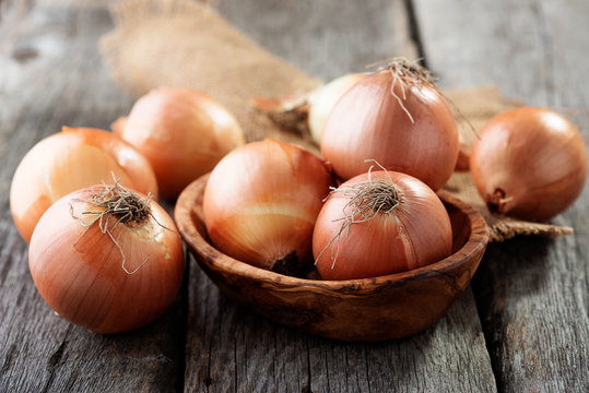 Fresh raw onions on wooden background.