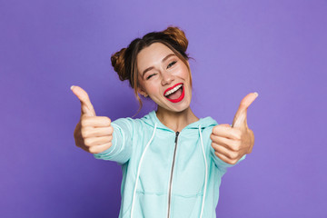 Portrait of astonished woman with two buns shouting and showing thumbs up meaning good result or choice, isolated over violet background in studio