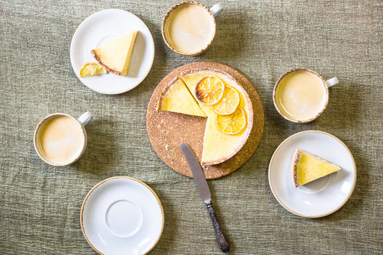 Lemon tart on the table among saucers and cups of coffee. Homemade pastries and homemade cosiness. Top view, flat lay