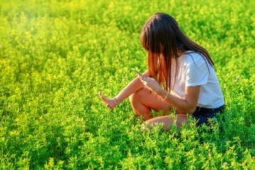Manicurist girl young woman  taking photo with cell phone of her nails on nature spring summer background. Beauty, fashion and technology concept.