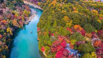 Aerial view boat on the river bring tourist people to enjoy autumn colors along katsura river to Arashiyama mountain area during fall season in Arashiyama, Kyoto, Japan.