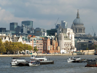 The city of london financial district showing current construction work on new large developments, taken from the thames south bank with historic buildings