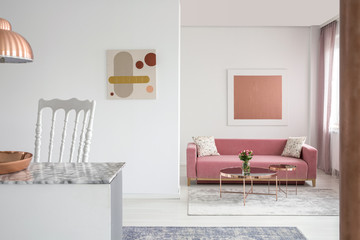 Real photo of paintings in a spacious living room interior with a pink sofa and copper coffee table