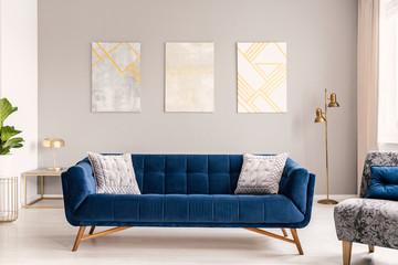 Fototapeta Elegant living room interior with a comfortable big blue velvet sofa and gold decorations. Real photo. obraz