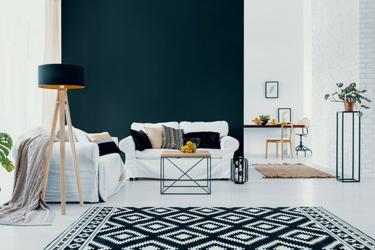 White couch against black wall in modern living room interior with patterned carpet. Real photo